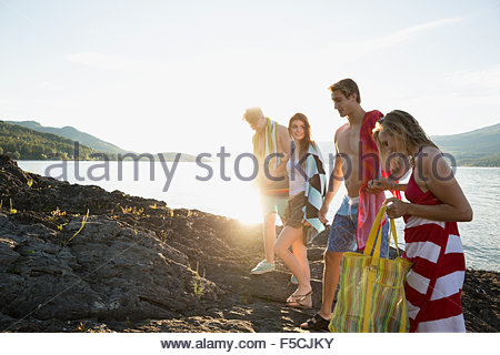 Young friends with towels on rocks at lakeside - Stock Photo