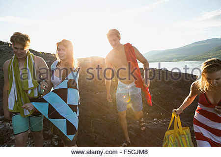 Young friends with towels on rocks sunny lakeside - Stock Photo