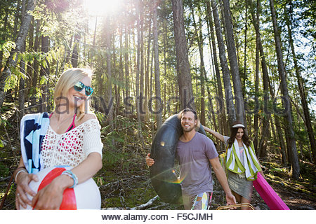 Young friends carrying pool rafts under trees - Stock Photo