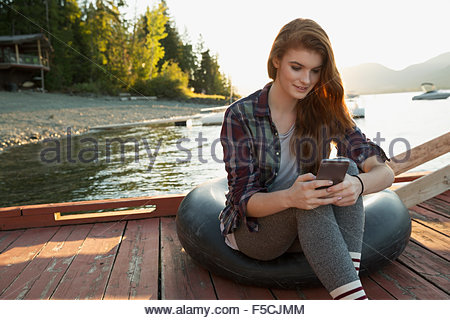 Young woman texting on lake dock - Stock Photo