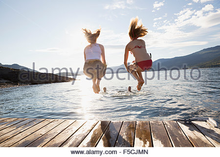 Young women jumping from dock into lake - Stock Photo