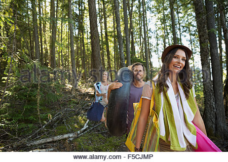 Smiling friends carrying towels and pool rafts woods - Stock Photo
