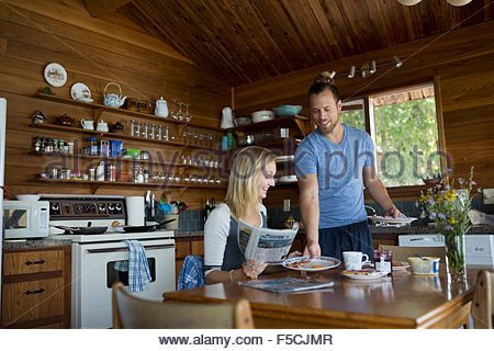 Young man serving woman breakfast in cabin kitchen - Stock Photo