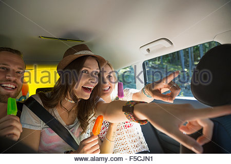 Enthusiastic friends pointing eating flavored ice in car - Stock Photo