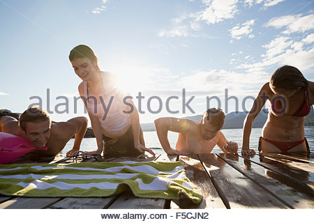 Young friends climbing onto lake dock - Stock Photo