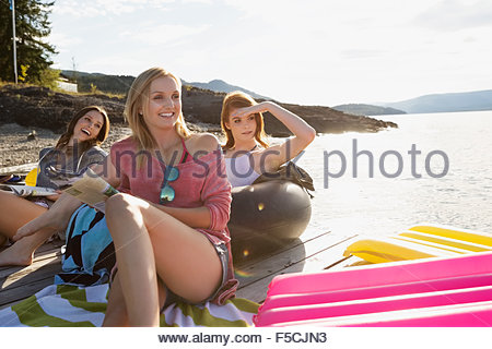 Young women relaxing hanging out sunny lake dock - Stock Photo