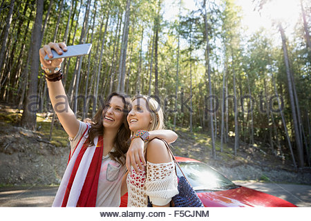 Young women taking selfie outside car in woods - Stock Photo