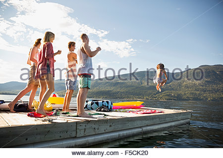 Young friends watching woman jump off lake dock - Stock Photo