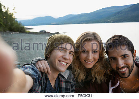 Portrait smiling young friends taking selfie at lakeside - Stock Photo