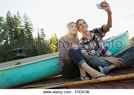 Smiling young couple taking selfie dock near canoe - Stock Photo