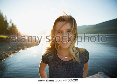 Portrait smiling young woman at sunny lakeside - Stock Photo