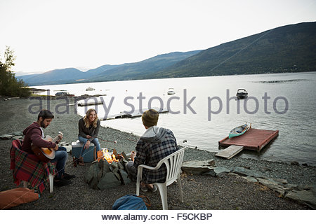 Young friends relaxing around lakeside campfire - Stock Photo