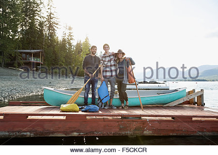 Portrait friends with canoe and paddles lake dock - Stock Photo