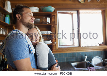 Young couple hugging in cabin kitchen - Stock Photo