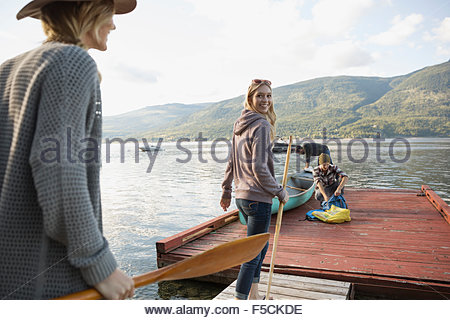 Young women carrying canoe paddles on lake dock - Stock Photo