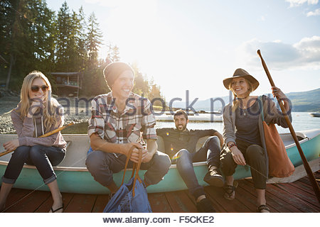 Young friends sitting in canoe on lake dock - Stock Photo
