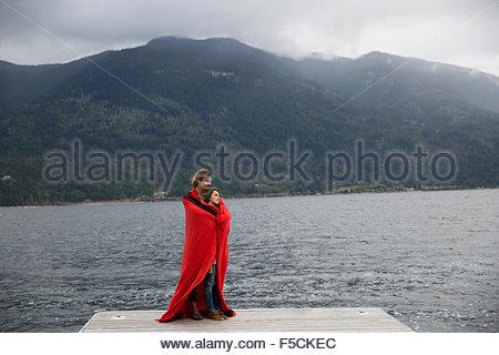 Romantic couple wrapped in blanket on lake dock - Stock Photo