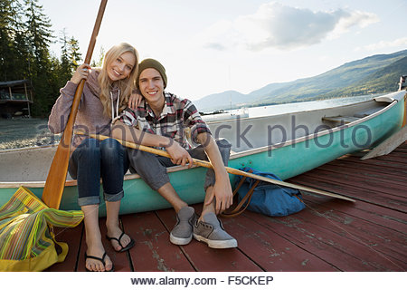 Portrait young couple with canoe and paddles dock - Stock Photo