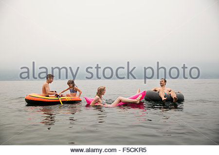 Family relaxing in pool rafts in lake - Stock Photo