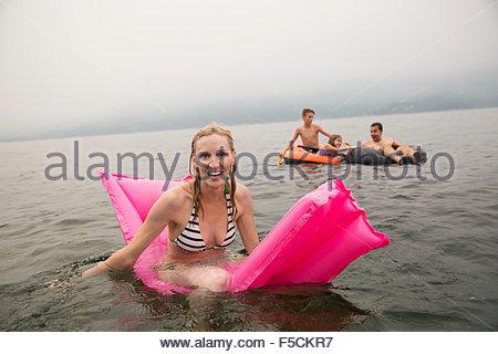 Portrait smiling woman on pool raft in lake - Stock Photo