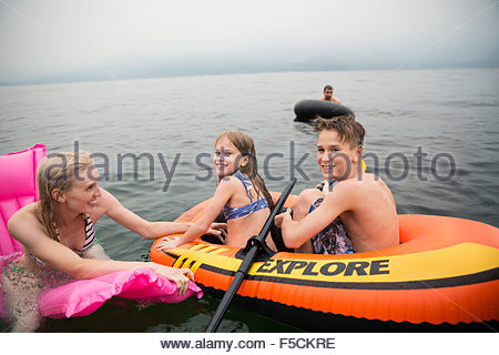 Family on inflatable rafts in lake - Stock Photo