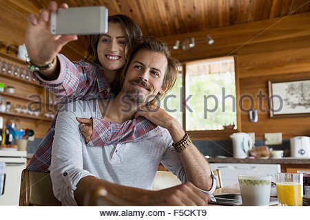 Affectionate young couple taking selfie in cabin kitchen - Stock Photo