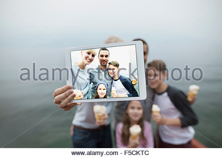 Family eating ice cream taking selfie lakeside - Stock Photo