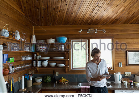 Man using digital tablet in cabin kitchen - Stock Photo