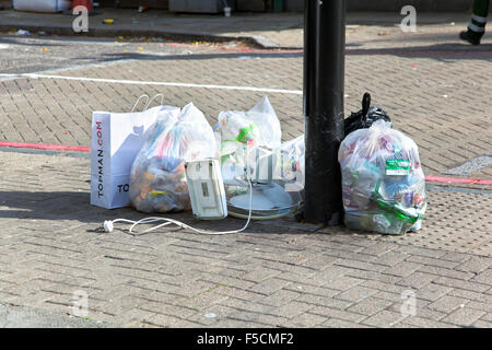 Bin bags and rubbish left on my a pole on the pavement, London, UK - Stock Photo