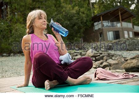 Mature woman drinking water yoga mat dock - Stock Photo