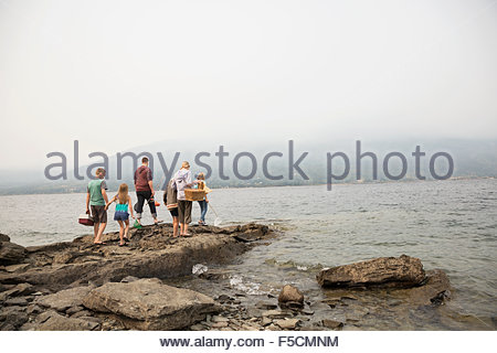 Family with fishing rods tackle box rocks lakeside - Stock Photo