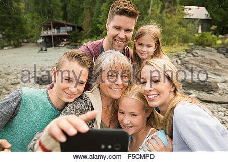 Multi-generation family taking selfie outside cabin - Stock Photo