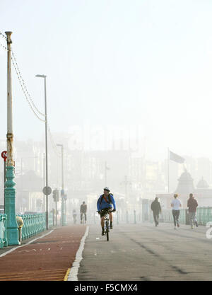 Brighton Sussex UK Monday 2nd November 2015 - Cyclists and runners have no problems with the foggy travel conditions - Stock Photo