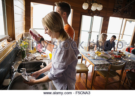 Couple washing dishes in cabin kitchen - Stock Photo