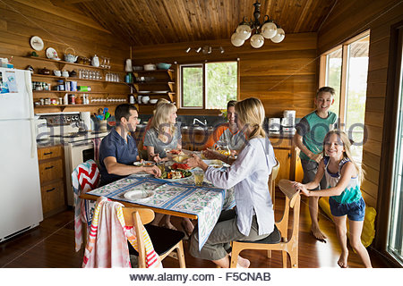 Family around table in cabin - Stock Photo