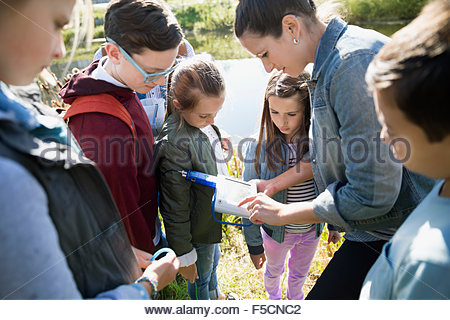 Science teacher students with equipment on field trip - Stock Photo