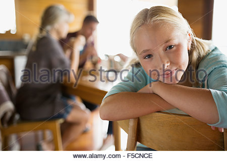 Close up portrait confident blonde girl leaning chair - Stock Photo