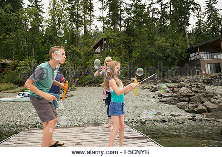 Family playing with bubbles on lake dock - Stock Photo