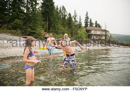 Family skipping stones in lake - Stock Photo