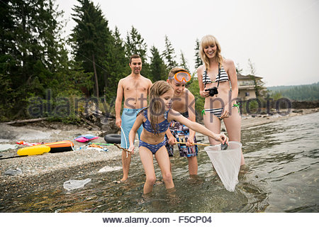 Family fishing with net in lake - Stock Photo