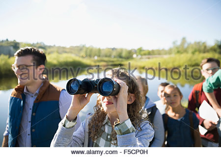 Curious schoolgirl with binoculars on field trip - Stock Photo