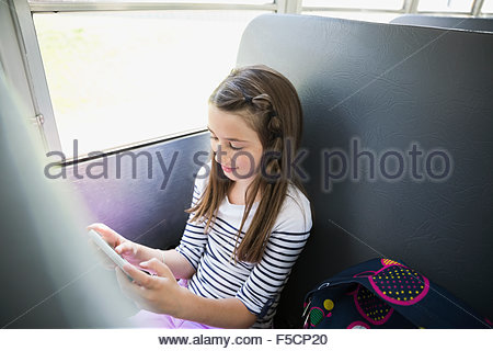 Schoolgirl texting with cell phone on school bus - Stock Photo
