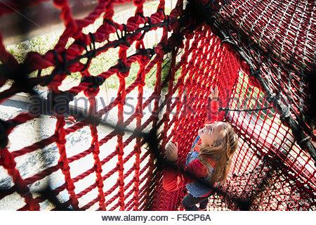 Girl climbing rope net at playground - Stock Photo