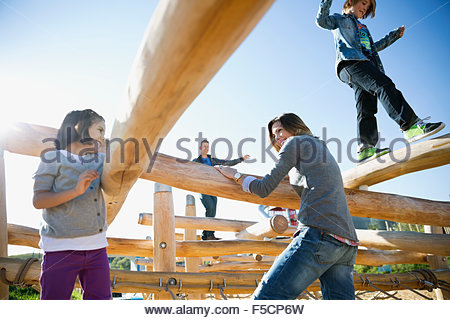 Family playing on logs at sunny playground - Stock Photo
