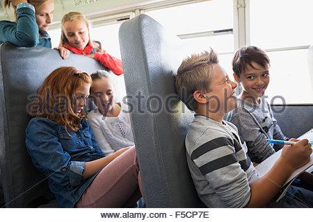 School kids riding school bus - Stock Photo