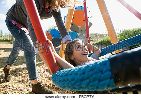 Mother pushing daughter on swing at sunny playground - Stock Photo