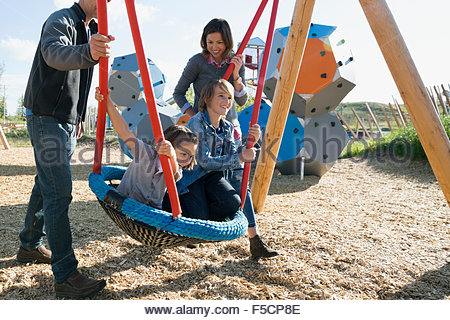 Family swinging at sunny playground - Stock Photo