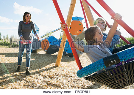 Mother pushing daughter and son in playground swing - Stock Photo