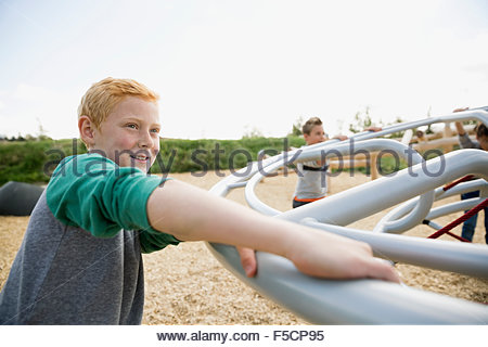 Boy playing with friends at playground - Stock Photo