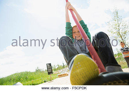 Boy playing on rope swing at sunny playground - Stock Photo